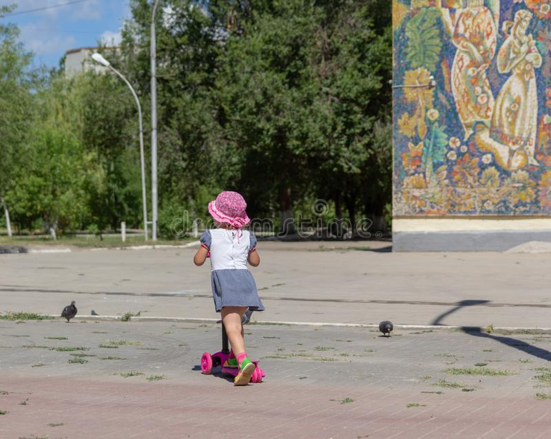Cute child skilfully skates on a pink two-wheeled scooter on a s. Ummer sunny day royalty free stock photo