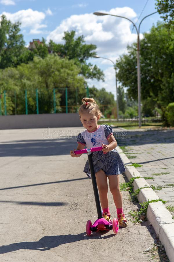 Cute child skilfully skates on a pink two-wheeled scooter on a s. Ummer sunny day royalty free stock photos
