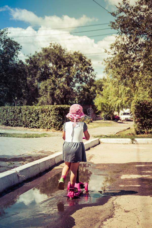Cute child skilfully skates on a pink two-wheeled scooter on a s. Ummer sunny day royalty free stock images