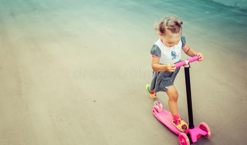 Cute child skilfully skates on a pink two-wheeled scooter on a s. Ummer sunny day stock photo