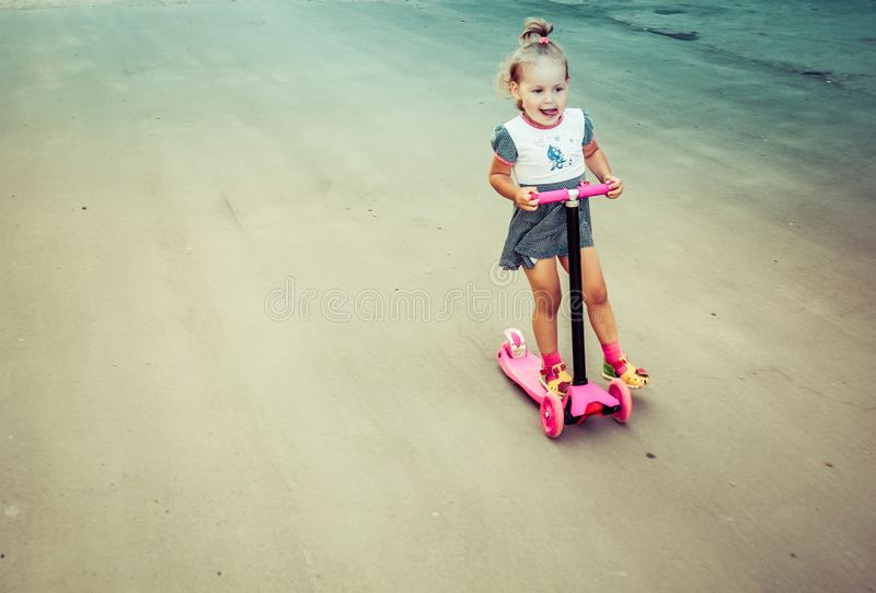 Cute child skilfully skates on a pink two-wheeled scooter on a s. Ummer sunny day stock image