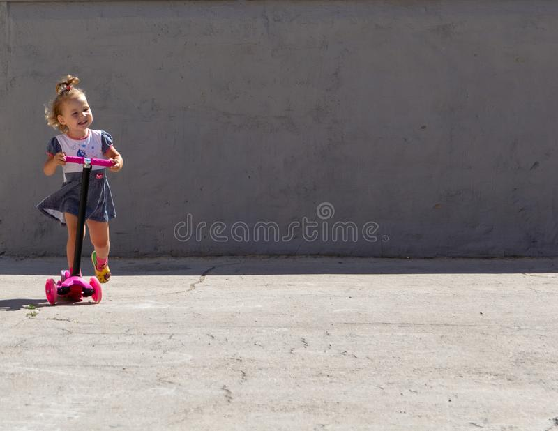 Cute child skilfully skates on a pink two-wheeled scooter on a s. Ummer sunny day royalty free stock image