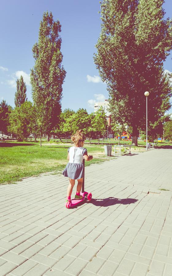 Cute child skilfully skates on a pink two-wheeled scooter on a s. Ummer sunny day royalty free stock photography