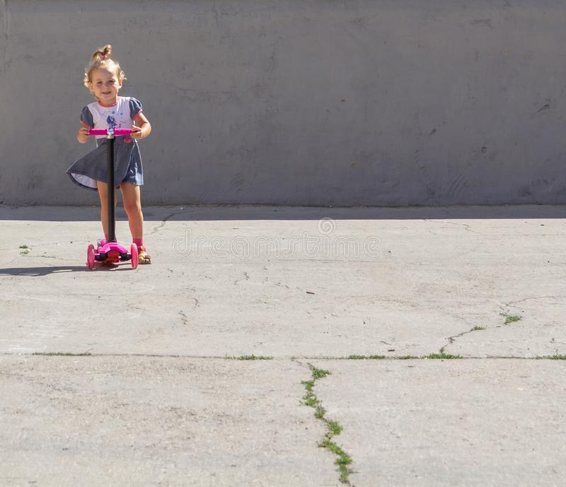 Cute child skilfully skates on a pink two-wheeled scooter on a s. Ummer sunny day stock images