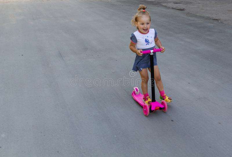 Cute child skilfully skates on a pink two-wheeled scooter on a s. Ummer sunny day stock photos