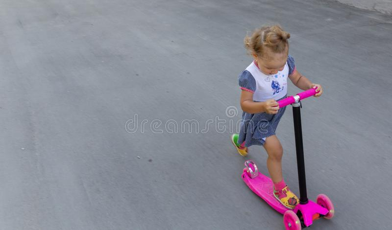 Cute child skilfully skates on a pink two-wheeled scooter on a s. Ummer sunny day stock photography