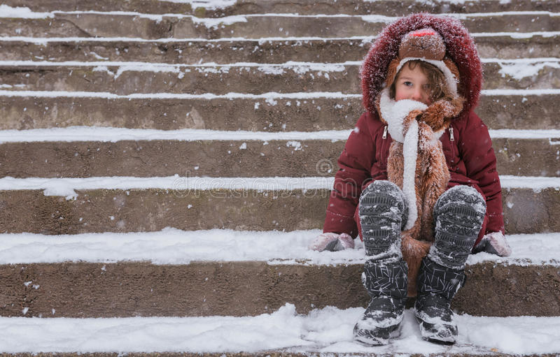 Cute child on the snow. Sad child sitting on the stairs covered with snow royalty free stock photos