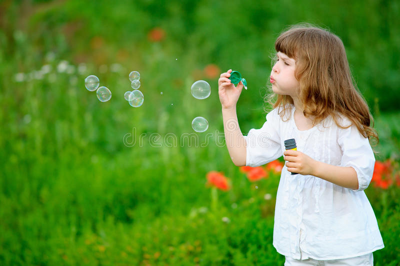 Cute child starts soap bubbles royalty free stock photos
