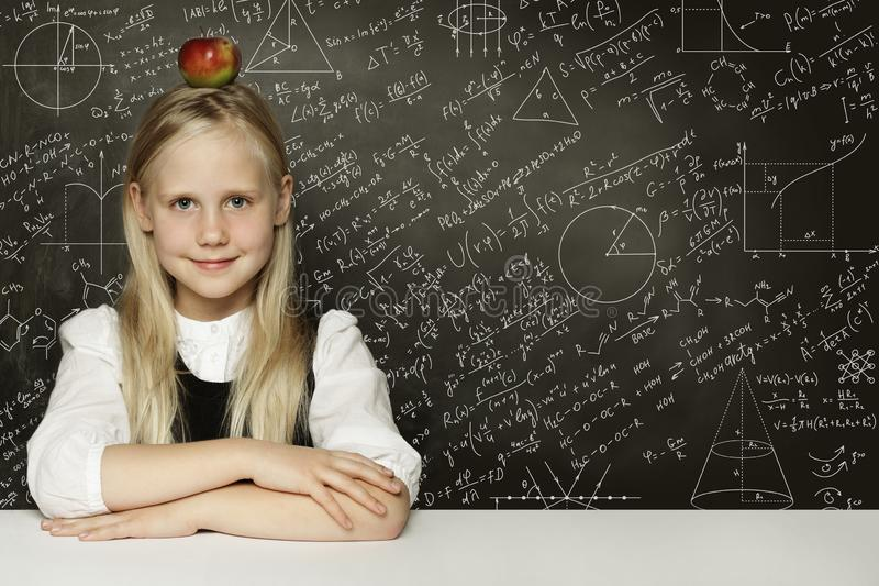Cute child student girl with red apple on head. Blackboard background with science formulas. Learning science concept royalty free stock photo