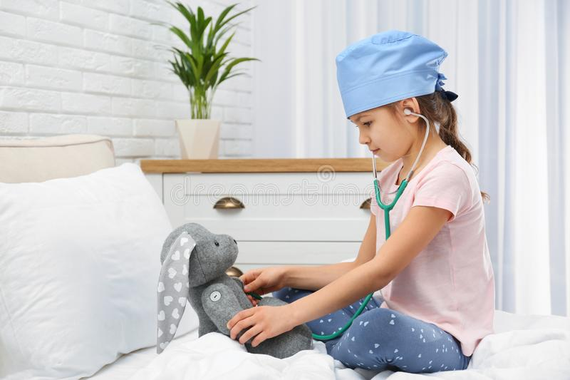 Cute child  with stuffed toy on bed in hospital ward royalty free stock images