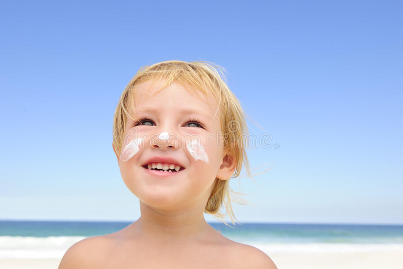Cute child with sunscreen at the beach stock images