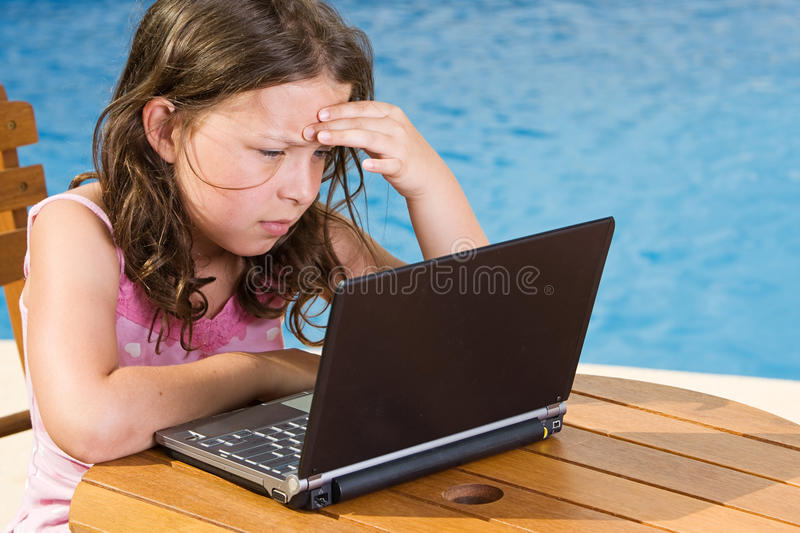 Cute Child Using her Laptop by the Pool stock photos