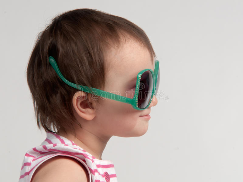 Cute child wearing glasses in a wrong way. Side view royalty free stock photo