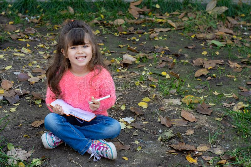 Cute child writing in notebook using pen and smiling. Four years old kid sitting on grass. Space for advertising text royalty free stock photography