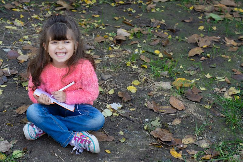 Cute child writing in notebook using pen and smiling. Four years old kid sitting on grass. Space for advertising text royalty free stock image