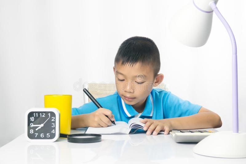 Cute child writing and working on work desk. Asian child boy is active and wisdom for working. He sitting on chair on white gray fabric background royalty free stock image