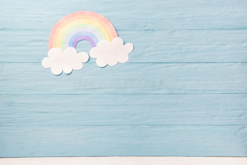 Cute children or baby background, white clouds with rainbow on the blue wooden background royalty free stock images
