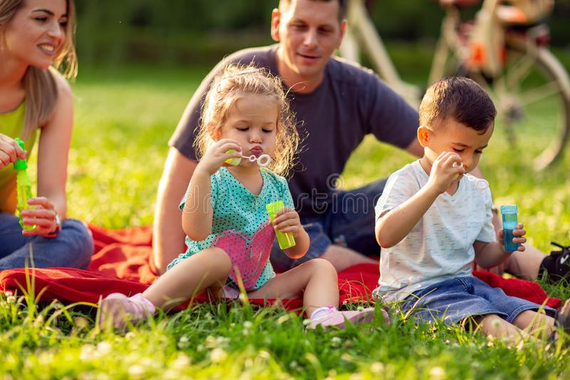 Children blow soap bubbles outdoor- Happy family in the park tog. Cute children blow soap bubbles outdoor- Happy family in the park together on a sunny day royalty free stock photos