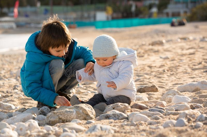 Cute children, boy brothers, playing on the beach with sand pebbles on sunset royalty free stock photography