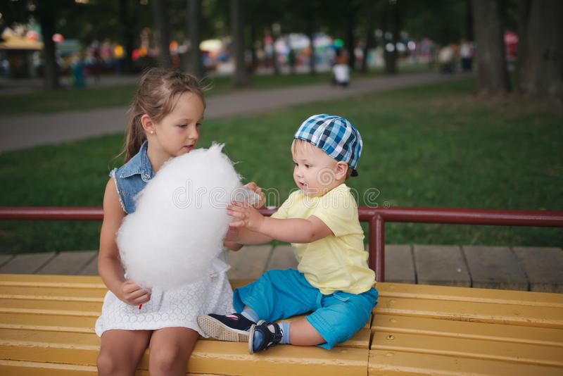 Cute children with cotton candy in park royalty free stock images