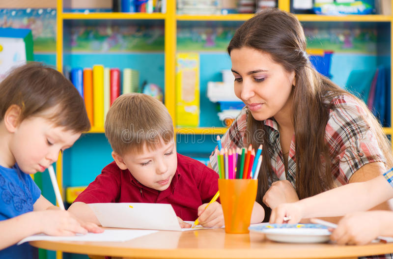 Cute children drawing with teacher at preschool class stock images