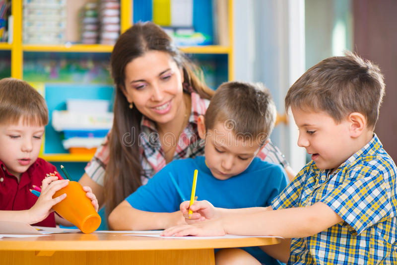 Cute children drawing with teacher at preschool class royalty free stock photography