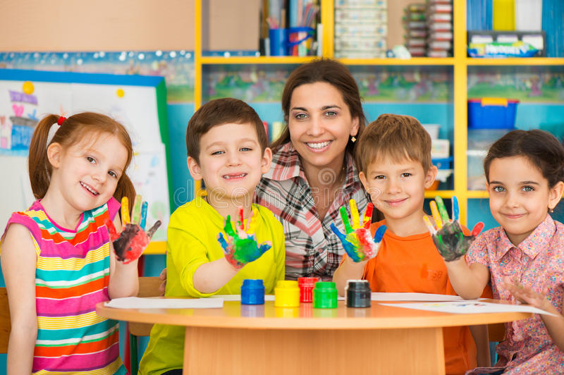 Cute children drawing with teacher at preschool class. Cute little children drawing with teacher at preschool class stock photos