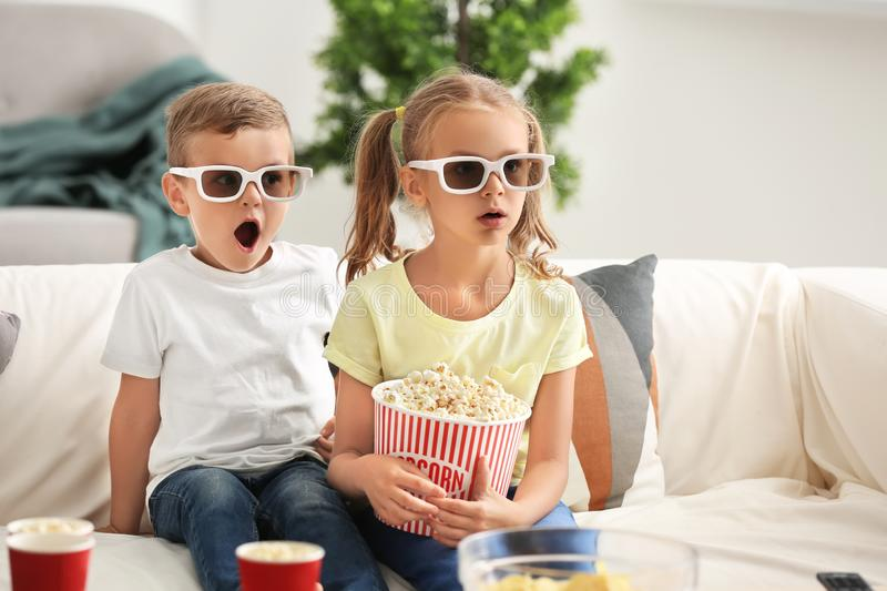 Cute children eating popcorn while watching TV at home stock image