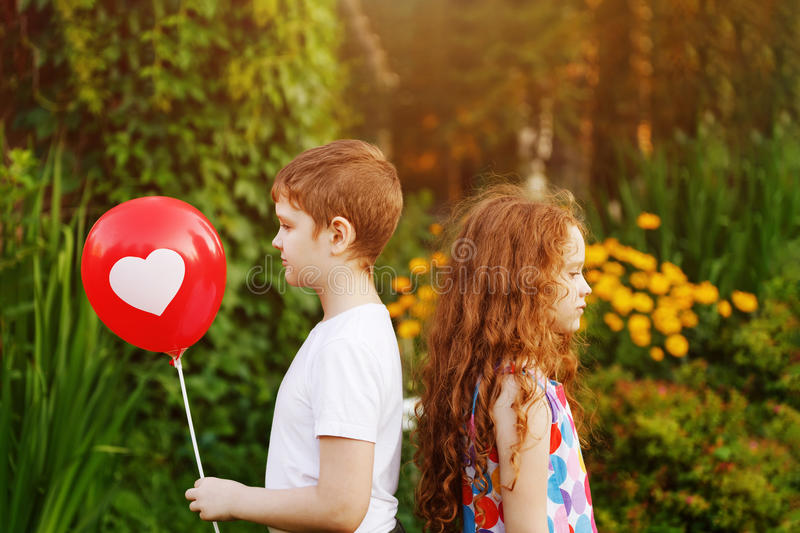 Cute children hold red balloons with heart in summer park. Valentines day background stock images