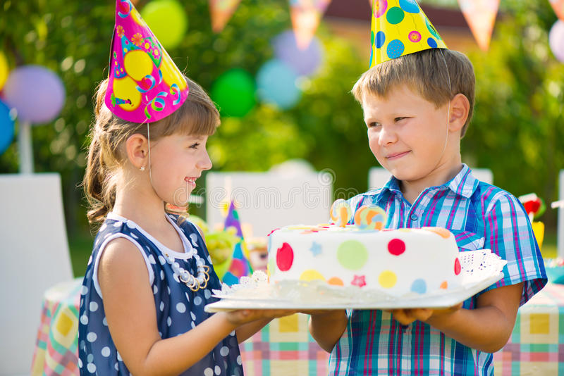 Cute children in love holding cake. At birthday party stock photography