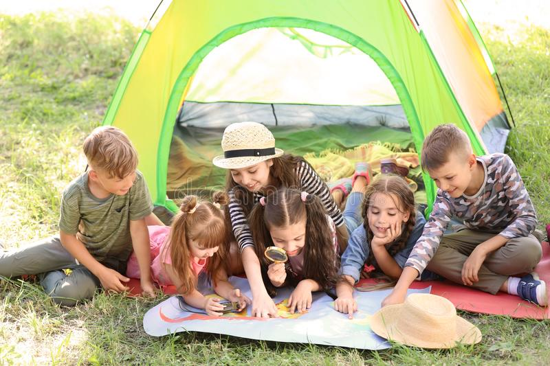 Cute children with map near tent outdoors. Summer camp royalty free stock image
