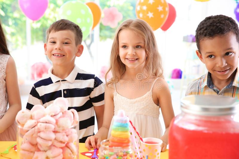 Cute children near table with treats at birthday party indoors stock photography
