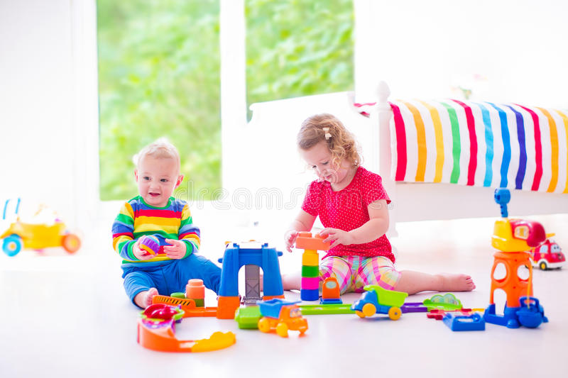 Cute children playing with toy cars. Two happy children playing with toy cars, cute curly toddler girl and a funny baby boy, brosther and sister, sitting on the stock images