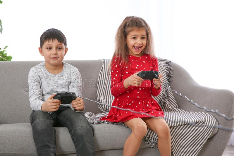 Cute children playing video game on sofa in room royalty free stock photography