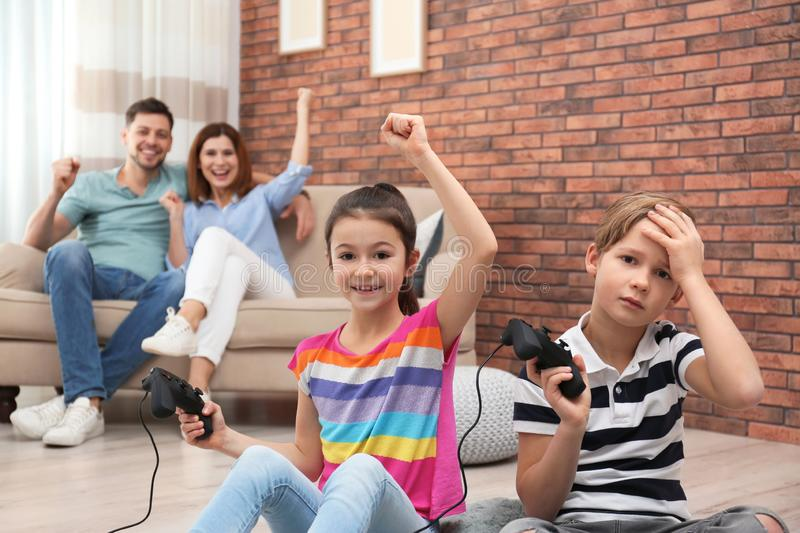 Cute children playing video games while parents resting on sofa. At home royalty free stock photography