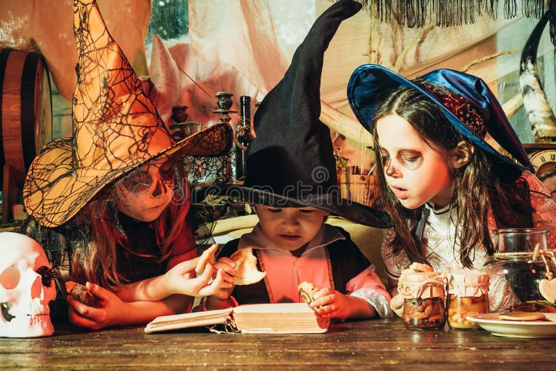Cute children in scary costumes reading horror stories in old house during Halloween party. Kids smiling on a Halloween royalty free stock photos