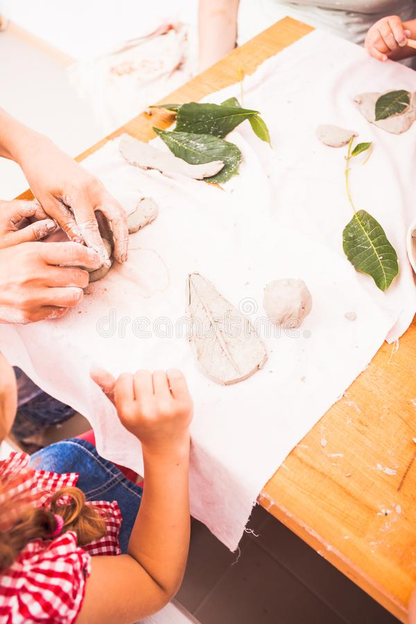 Happy children are engaged with modeling clay. Cute children sculpt something from grey plasticine in kindergarten royalty free stock images