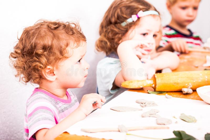 Happy children are engaged with modeling clay. Cute children sculpt something from grey plasticine in kindergarten stock photos