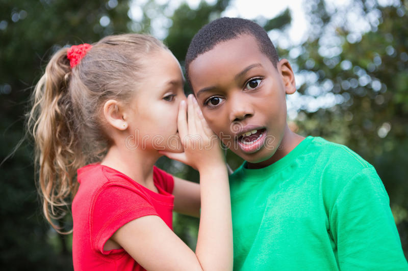 Cute children sharing gossip outside royalty free stock photos