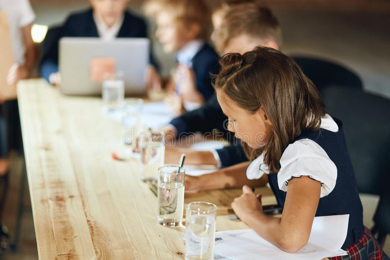 Cute children in shcool uniform taking part in the meeting. Writing information on sheets of paper, close up side view photo. blurred background royalty free stock photography