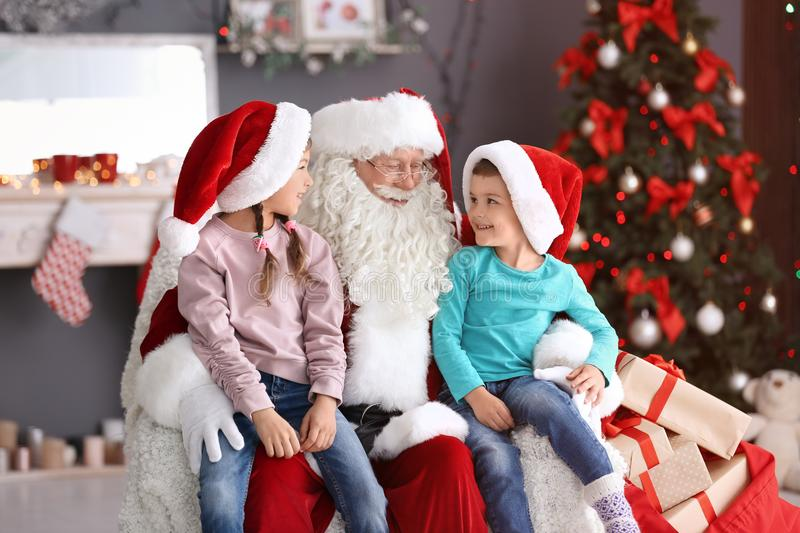 Cute children sitting on authentic Santa Claus` knees indoors stock photography
