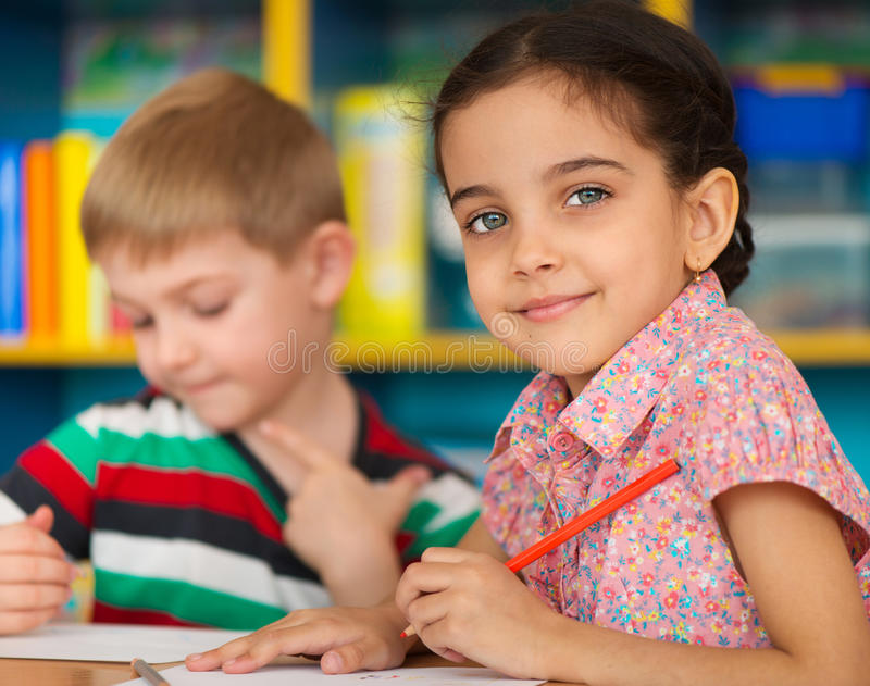 Cute children study at daycare. Cute little children drawing and studying at daycare stock images
