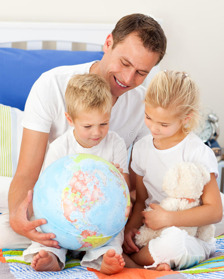 Cute children and their father looking at a glob stock photos