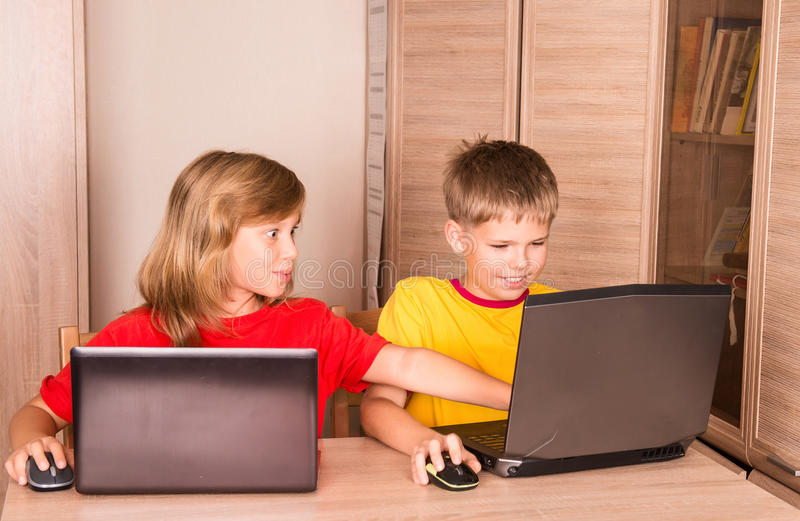 Cute children using laptops at home. Education, school, technology and internet concept - little students with laptop pc. royalty free stock images