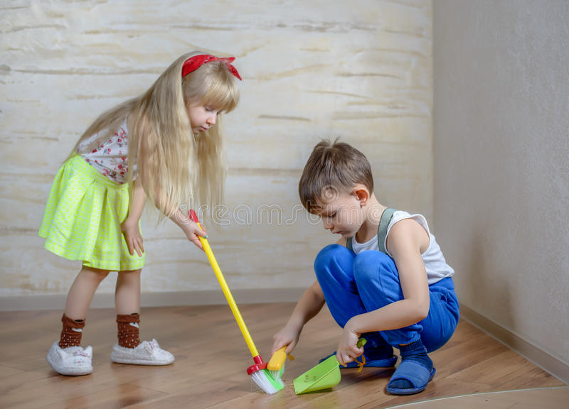 Cute children using toy broom and dustpan royalty free stock photography