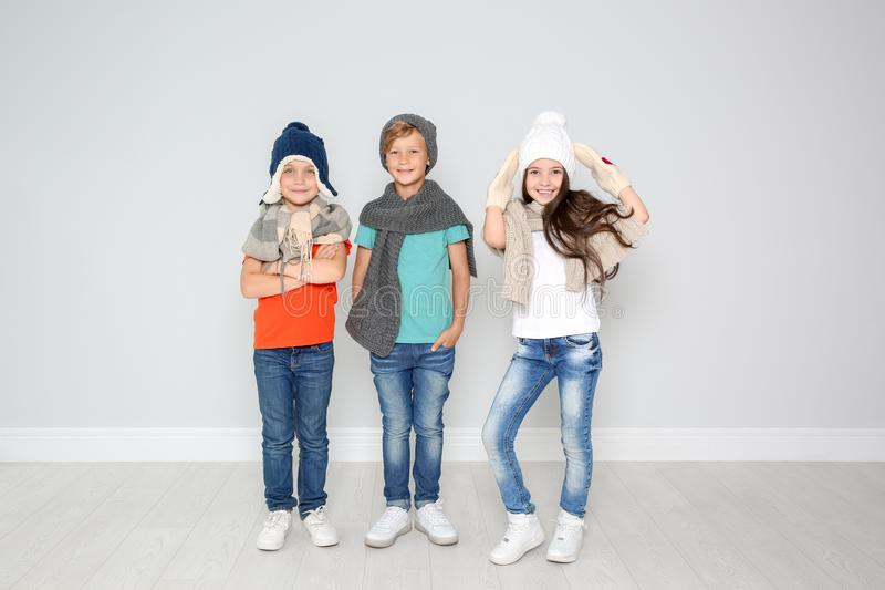 Cute children in warm clothes posing near light wall. Christmas celebration royalty free stock photography