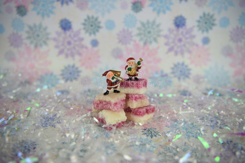 Cute Christmas food photography picture with old fashioned English coconut ice sweets with Santa Claus music playing decorations stock images