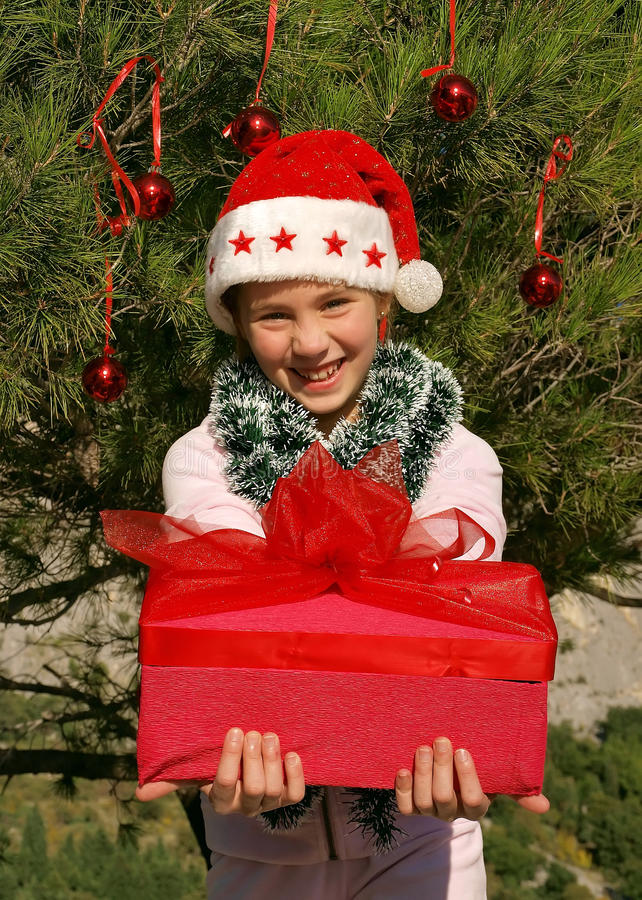 Cute Christmas girl giving a gift 1 stock photo