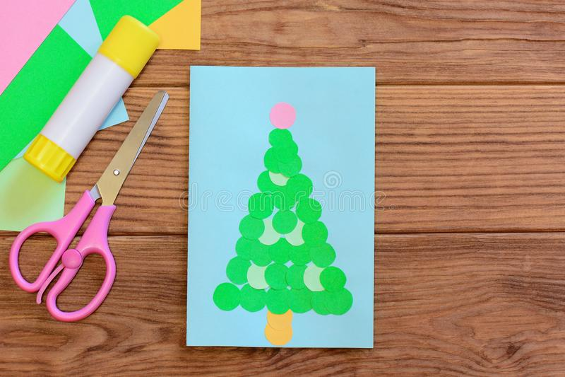 Cute Christmas tree card design. Christmas greeting card, colored paper sheets, scissors, glue stick on a wooden background. Handmade Christmas greeting card royalty free stock photos