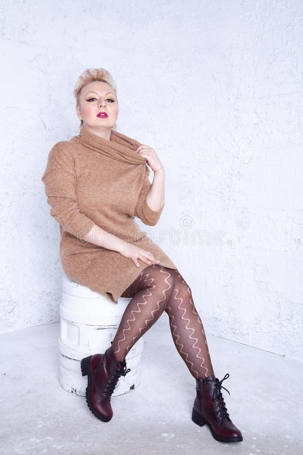 Cute chubby girl with short hair in big warm brown sweater and pantyhose on white background in Studio royalty free stock images